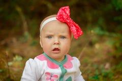 Ein kleines Mädchen in einer weißen Klage mit einem roten Bogen Lizenzfreie Stockfotografie