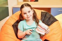 Ein kleines Mädchen in einer zahnmedizinischen Klinik, die eine zahnmedizinische Attrappe hält lizenzfreie stockbilder