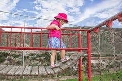 Ein kleines Mädchen geht auf die Brücke im Spielplatz Kind-` s Unterhaltung stockfotografie