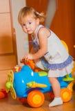 Ein kleines Mädchen geht auf ein Spielzeugauto Stockfoto
