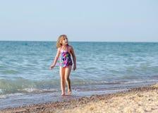 Ein kleines Mädchen geht entlang den Strand, der oben schaut Lizenzfreie Stockfotos