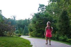 Ein kleines Mädchen geht entlang den Weg Stockfoto