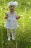 Ein kleines Mädchen geht glücklich unter dem Löwenzahn Lizenzfreie Stockfotos