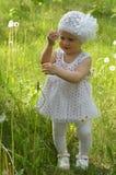 Ein kleines Mädchen geht glücklich unter dem Löwenzahn Stockbild