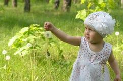 Ein kleines Mädchen geht glücklich unter dem Löwenzahn Stockfoto