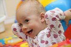 Ein kleines Mädchen hat einen Spaß mit dem Wasserball Stockfotos
