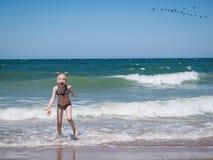 Ein kleines Mädchen im Schrecken vom rasenden Meer Lizenzfreie Stockfotos