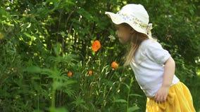 Ein kleines Mädchen inhaliert den Duft von Blumen im Garten an einem sonnigen Tag stock video
