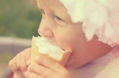 Ein kleines Mädchen isst Eiscreme und geschmiert ihrem Gesicht Lizenzfreie Stockfotografie