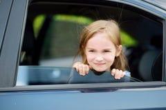 Ein kleines Mädchen ist das Haften ihr vorangehen heraus das Autofenster Lizenzfreies Stockbild
