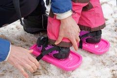 Ein kleines Mädchen 3-jährige, die ihn Schneeschuhe befestigt haben stockfotos