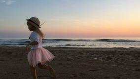 Ein kleines Mädchen läuft entlang den Strand bei Sonnenuntergang stock video footage