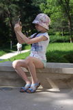 Ein kleines Mädchen macht Fotos mit einer Handykamera in der Natur, in den Bergen Stockfoto