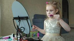 Ein kleines Mädchen mit dem roten Haar befestigt Haarnadeln auf Haar, versucht an Zusätze, Blicke im Spiegel, Make-up, Gesicht, M stock footage