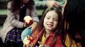 Ein kleines M?dchen mit der Familie, die Picknick in der Herbstnatur, Apfel essend hat stock video
