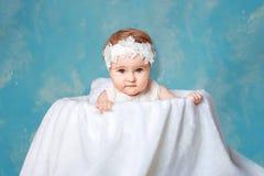 Ein kleines Mädchen mit einem Kranz auf ihrem Kopf, der in einem großen Korb sitzt stockfotografie
