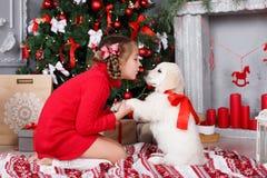 Ein kleines Mädchen mit einem Welpe golden retriever auf einem Hintergrund des Weihnachtsbaums Lizenzfreie Stockfotos