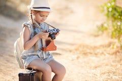 Ein kleines Mädchen mit einer alten Kamera auf einer Landstraße, die auf einem Koffer sitzt Stockbild