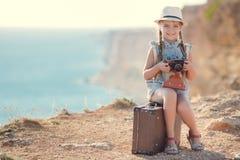 Ein kleines Mädchen mit einer alten Kamera auf einer Landstraße, die auf einem Koffer sitzt Lizenzfreie Stockbilder