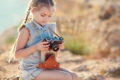 Ein kleines Mädchen mit einer alten Kamera auf einer Landstraße, die auf einem Koffer sitzt Stockbilder