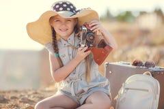 Ein kleines Mädchen mit einer alten Kamera auf einer Landstraße, die auf einem Koffer sitzt Lizenzfreies Stockbild