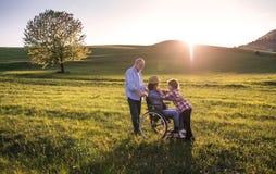 Ein kleines Mädchen mit ihren älteren Großeltern mit Rollstuhl auf einem Weg draußen in der Natur Stockbilder