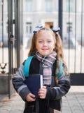 Ein kleines Mädchen mit roten Endstücken in ihren Händen hält ein Buch vor der Schule lizenzfreie stockbilder