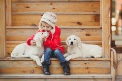 Ein kleines Mädchen mit zwei Welpe golden retriever Stockfotografie