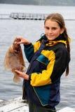 Ein kleines Mädchen in Norwegen hat einen großen Fisch in der Hand Lizenzfreie Stockbilder