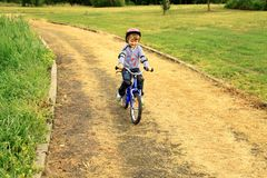 ein kleines Mädchen reitet ein Fahrrad im Park Stockfotos