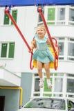 Ein kleines Mädchen reitet ein Schwingen und ein Lachen Das Konzept der Kindheit, Lebensstil, Erziehung, Kindergarten stockbilder