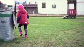 Ein kleines Mädchen sah, hob auf und warf heraus den Abfall stock footage