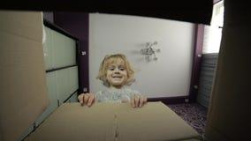 Ein kleines Mädchen schaut im Kasten, um eine Überraschung zu empfangen Das Kind öffnete einen Kasten stock footage