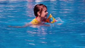Ein kleines Mädchen schwimmt im Pool Das Kind ist, spritzend badend und im blauen Pool stock video
