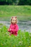 Ein kleines Mädchen sitzt allein im Gras auf der Bank von einem See, ein Fluss r lizenzfreies stockbild