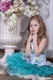 Ein kleines Mädchen sitzt auf dem Boden nahe einem großen Vase mit Blumen Stockbild