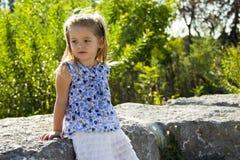 Ein kleines Mädchen sitzt auf einem Felsen Lizenzfreie Stockbilder