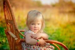 Ein kleines Mädchen sitzt auf einem Stuhl Stockfoto