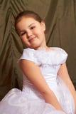 Ein kleines Mädchen sitzt nachdenklich. Lizenzfreie Stockfotografie