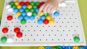 Ein kleines Mädchen spielt ein Spiel, ausarbeitet ein mehrfarbiges Mosaik, das sich entwickelt, entwickelt Bewegungsfähigkeiten u stock video