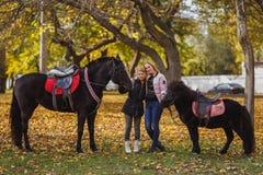 Ein kleines Mädchen, steht mit ihrer Mutter in einem Herbstpark und hält ein Pferd und ein Pony Lizenzfreies Stockfoto