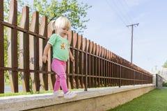 Ein kleines Mädchen stiehlt vom Rand eines Zauns Stockbilder
