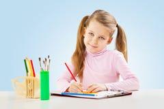 Ein kleines Mädchen am Tisch lizenzfreie stockfotos
