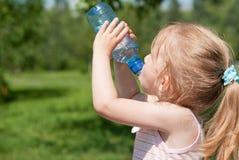 Ein kleines Mädchen trinkt Trinkwasser Stockbild