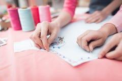 Ein kleines Mädchen und eine Frau konstruieren zusammen Kleidung lizenzfreies stockbild