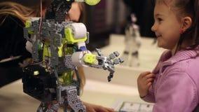 Ein kleines Mädchen und eine Frau sprechen mit einem Roboter Moderne Robotertechnologien Künstliche Intelligenz kybernetisch stock footage