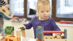 Ein kleines Mädchen und ihr älterer Bruder spielen pädagogische Spielwaren stock footage
