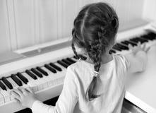 Ein kleines Mädchen, welches das Klavier spielt: schauen Sie von der Rückseite Stockfotografie