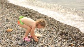 Ein kleines Mädchen wirft Steine in das Meer, Sommerferien durch das Wasser stock video footage