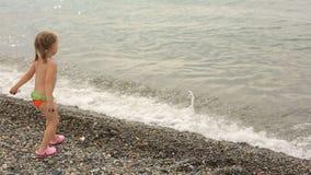 Ein kleines Mädchen wirft Steine in das Meer, Sommerferien durch das Wasser